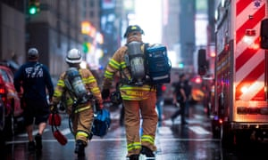 Firefighters are seen after a helicopter crash landed on top of a building in midtown Manhattan in New York