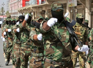 Shia militiamen parade in northern Iraq last June.