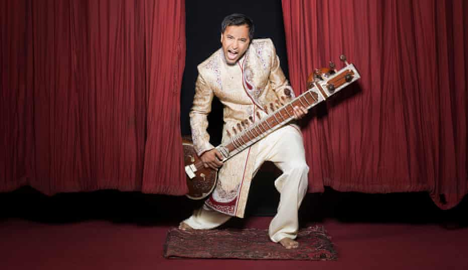 Rhik Samadder pretending to play a sitar in front of red theatre curtains