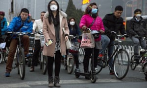 Pedestrians wearing mask against heavy pollution wait to cross a street in Beijing, The Chinese capital struggles with persistent pollution tied to rapid growth in number of cars and coal burning power plants powering the ever growing city.
