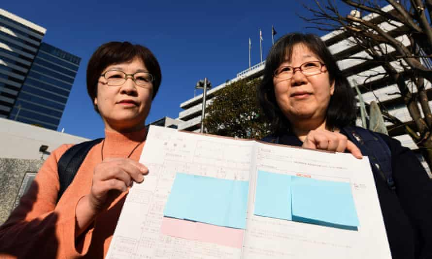 Yoko Ogawa and Chizuka Oe display their marriage registration form to journalists in front of a town hall in Tokyo.