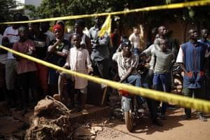 Children stand behind a police barricade outside the Radisson Blu hotel in Bamako, Mali.