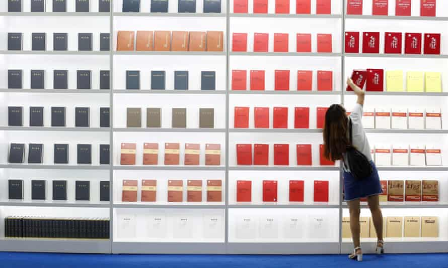 Time to reach higher? … a woman takes a book from a shelf at the 2017 international book fair in Beijing.