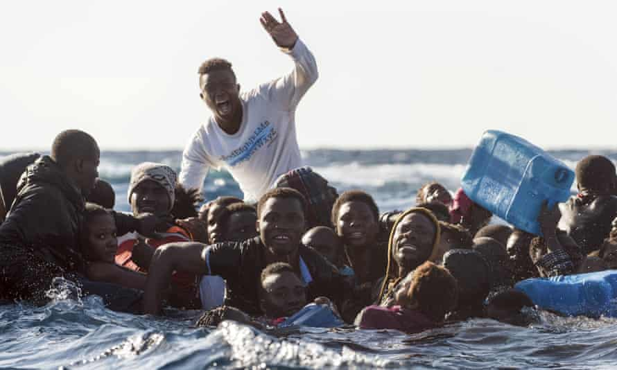 Migrants on a partially submerged dinghy in the Mediterranean Sea on 27 January 2018.