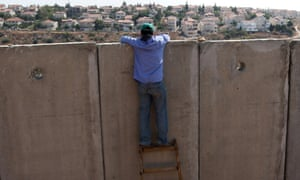 A Palestinian youth looks over the West Bank barrier.