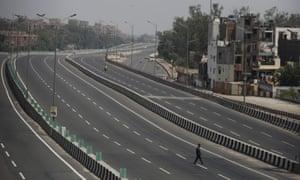 A man crosses an empty expressway in New Delhi