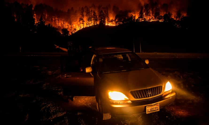 US-FIRE<br>People stop on the side of the road to watch as the Glass Fire slowly blazes down the hill side outside of Calistoga in Napa Valley, California on September 28, 2020. - The wildfire went from 1,500 acres to more than 15,000 acres overnight as winds spread embers across the valley. Tens of thousands of people were forced to flee their homes in California's Napa and Sonoma valleys on Monday as wildfires fanned by fierce winds ripped through the world-famous wine region. (Photo by Samuel Corum / AFP) (Photo by SAMUEL CORUM/AFP via Getty Images)