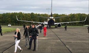 Passengers leave the plane at Stansted airport after the security alert.