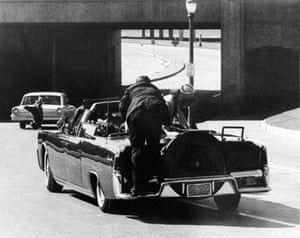 John F Kennedy slumps down in the back seat of the presidential limousine after being fatally shot in Dallas, with Jacqueline Kennedy leaning over him while a Secret Service agent stands on the bumper