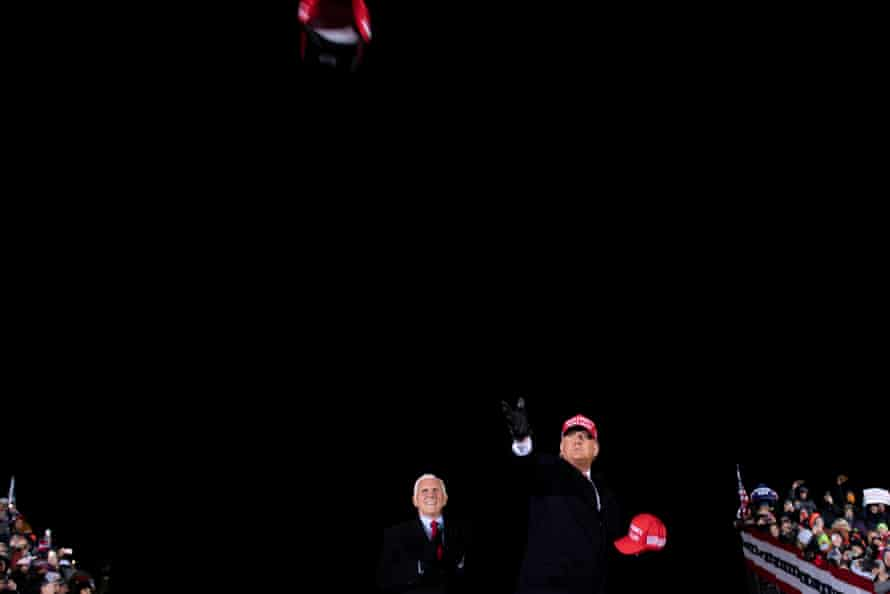 Donald Trump throws hats to supporters at his final rally in Grand Rapids, Michigan.