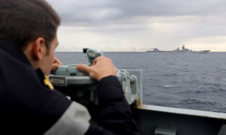An HMS Richmond crew member watches the Russian aircraft carrier Admiral Kuznetsov in the North Sea being escorted on its voyage to the Mediterranean Sea.