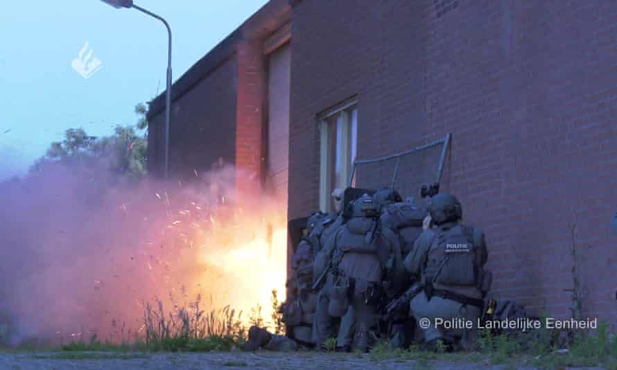 Photo of police huddle in a group against the wall of a building as a large explosion goes off by the door