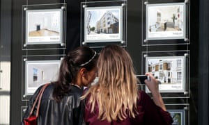 Two women view an estate agent's window
