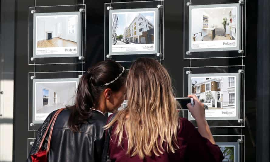 Two young women look at property ads in an estate agent's window