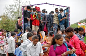 Migrant workers and their families board a truck in Ahmedabad to return to their villages