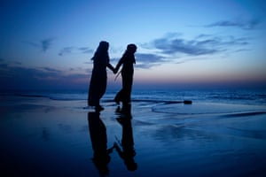 Taking a moment for themselves two young Palestinian girls walk along the beach in Gaza City