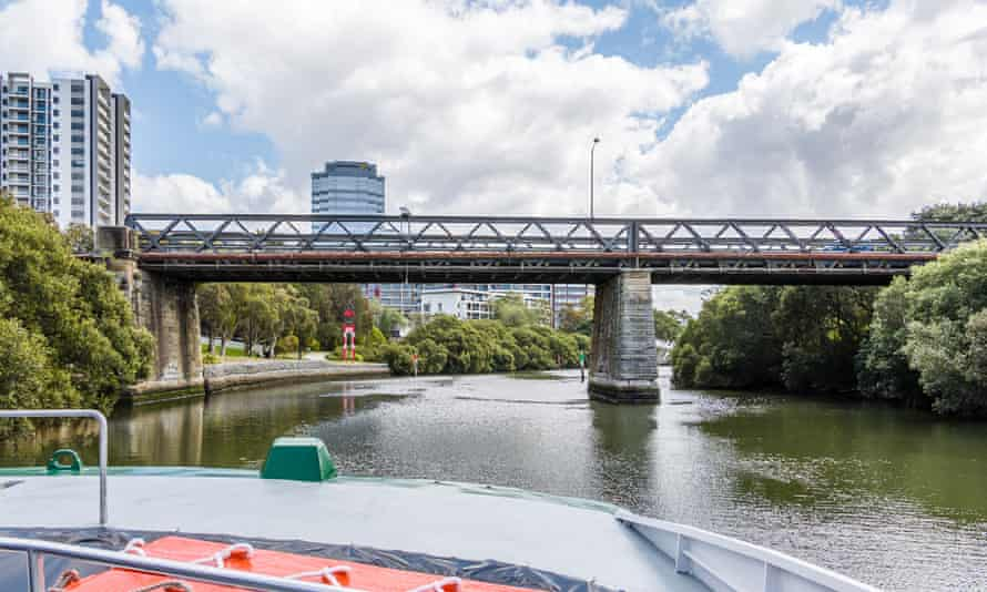 A Rivercat ferry (not one of the new River Class ferries) prepares to pass under the Gasworks Bridge on the Parramatta River. The new River Class ferries, purchased from Indonesia, are too high for passengers to be on the top deck when it goes under the bridge.