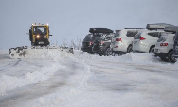 Mesin salju membersihkan tempat parkir mobil di Guthega di hulu Sungai Snowy di NSW.