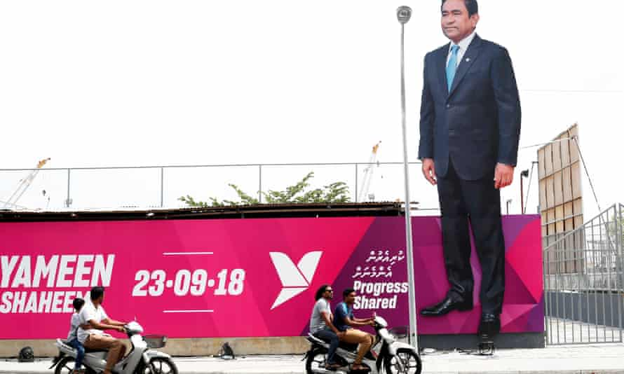People ride motorcycles past an image of Maldives President Abdulla Yameen