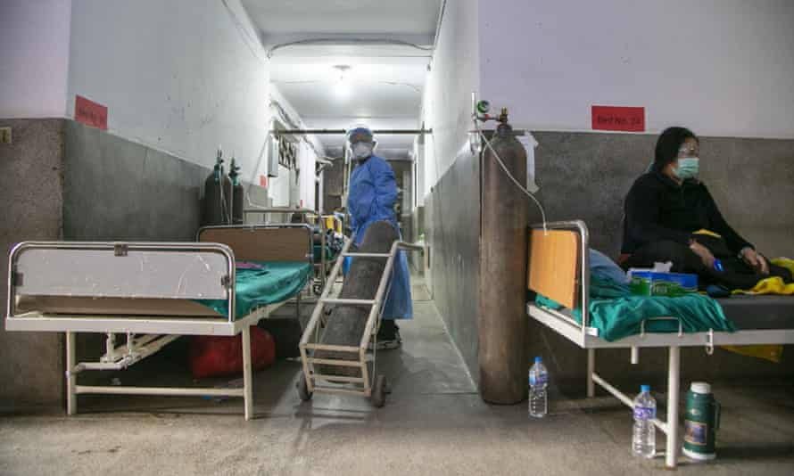 A Nepalese paramedic wheels in an oxygen cylinder as a Covid patient rests on a bed in the corridor of a government-run hospital in Kathmandu