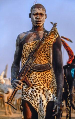 Dinka warrior with leopardskin and Kalashnikov rifle, South Sudan, 2006.