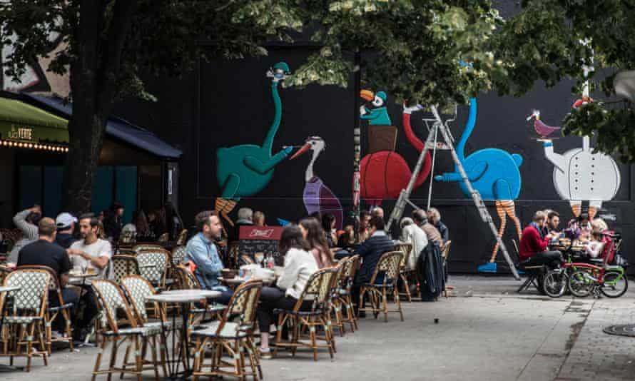 People sit in a Paris street cafe next to a mural about frontline workers
