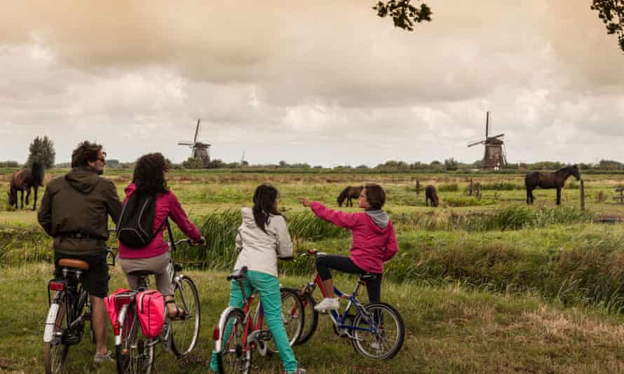 A family on bikes takes in the sights of Kinderdijk.