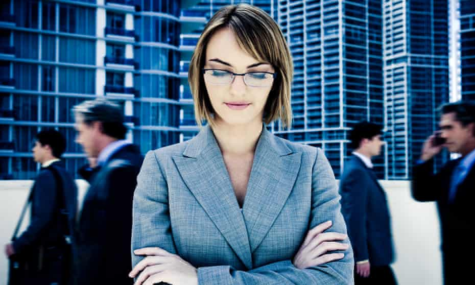Young businesswoman staring down with motion blurred businessmen walking by