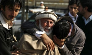 Relatives grieve after a suicide bomber targeted a police checkpoint in Peshawar, Pakistan