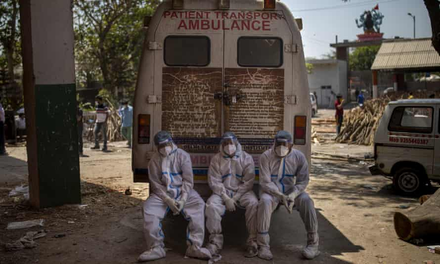 Three workers in white PPE sit on the back step of an ambulance at a crematorium in New Delhi
