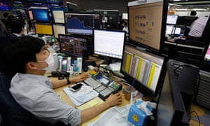 A trader wearing a protective mask works in front of monitors at the KEB Hana Bank in Seoul, South Korea, today