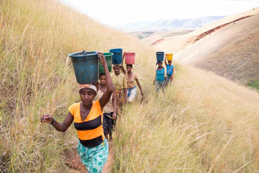A group of women carrying water climb up a hill on their way home to the village of Miarinarivo, Madagascar