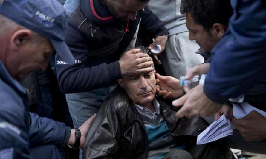 Greek police help a refugee who fainted after being turned back by Macedonian border authorities.