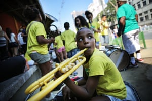 Young people from the Favela Brass band, who live in the Pereira da Silva favela, wait with donated instruments on the Olympic Boulevard to perform for tourists. About 40 students are part of the project which provides free music and English lessons to children from the community