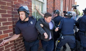 Police escort Jason Kessler away from his press conference in Charlottesville.