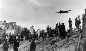 People watch a plane landing at Tempelhof airport during the Berlin blockade, August 1948.