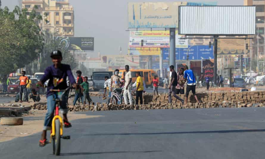 Protesters build a brick barrier blocking on a main road in the capital Khartoum, during a demonstration against rising prices on 24 January.