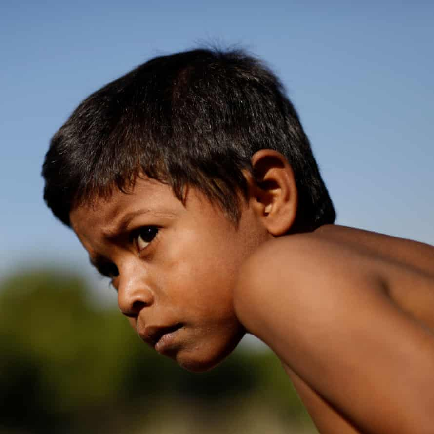 Jose, 7, travels on an open wagon of a freight train, 14 April