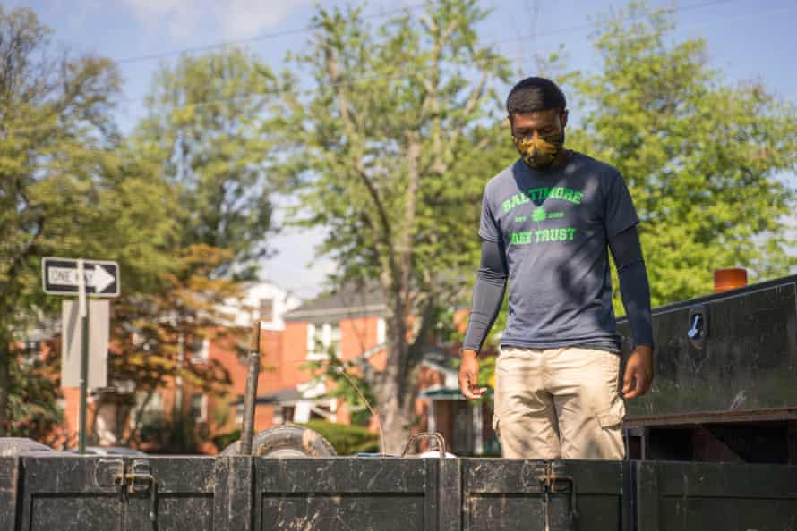 Kwamel Couther, foreman for Baltimore Tree Trust, unloads wheel barrows outside a school in East Baltimore.
