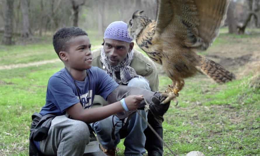 Rodney Stotts teaches student Javiare Harris to pick up his Eurasian eagle-owl, Mr Hoots.