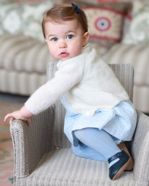 Princess Charlotte clambers on to a wicker chair.