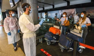 Airport staff wearing protective gear and travellers wearing face masks