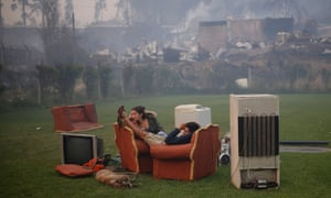 A young couple rest in a football field after a forest fire devastated Santa Olga.