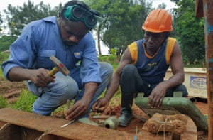 Lead mechanic Deograce, left, is watched by local mechanic Kabengele