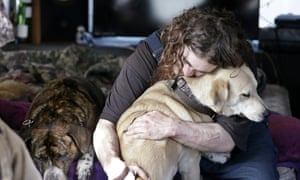 A man hugs his dog in a temporary city-approved area for people living in their vehicles in Seattle. The number of homeless people in the county that includes the city rose by 1,000 between 2016 and 2017.