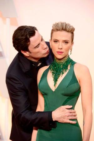 John Travolta kisses Scarlett Johansson as they arrive for the 87th ceremony