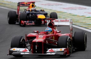 Ferrari's Fernando Alonso steers his car ahead of Red Bull 's Sebastian Vettel.