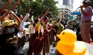 Pengunjuk rasa anti-pemerintah memberikan hormat tiga jari - gerakan yang digunakan oleh pengunjuk rasa dari film Hunger Games - saat mereka berkumpul untuk mendukung orang-orang yang ditahan di bawah undang-undang lese-keagungan di sebuah kantor polisi di Bangkok.