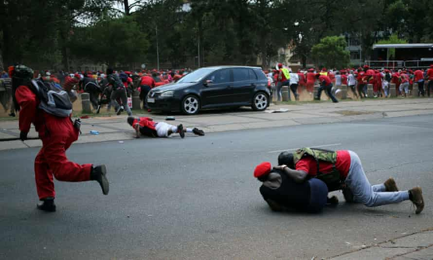 Protesters run for cover as police used water cannon to disperse a march outside the Union Buildings in Pretoria