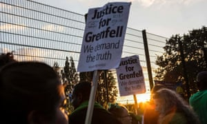 People take part in a silent walk past Grenfell Tower in west London.